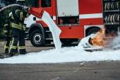 částečný pohled hasič hasí oheň s pěnou na ulici