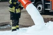 oříznutý snímek hasič hasí oheň s pěnou na ulici