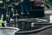 částečný pohled brigáda hasičů a vodní hadice na zem na ulici