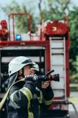 Selektivní fokus mužských hasič v přilbě s hadici na ulici