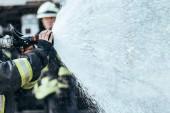 Fotografie částečný pohled hasič s hadice na vodu pro hašení požáru na ulici