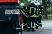 Selektivní fokus brigády hasiči stojící na hasičské auto na ulici