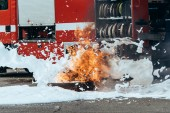 Fotografie close up view of extinguishing foam, flame and fire truck on street