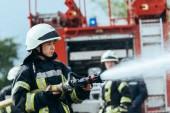 ženské hasič s hadice na vodu pro hašení požáru na ulici