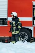 ženské hasič v ochranné jednotné postavení v pěna na ulici s červené hasičské auto za
