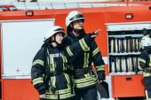 Hasiči v ochranných jednotné koukal s hasičský vůz za na ulici