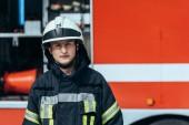 portrét hasič v jednotné, stojící na ulici s červené hasičské auto za