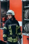 hasič v helma stojí na vůz s hadice s vodou uvnitř na ulici