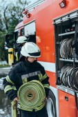 Feuerwehrmann legt Wasserschlauch in Lastwagen auf Straße