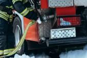 Teilansicht eines Feuerwehrmannes in Schutzuniform bei der Kontrolle des Wasserschlauchs