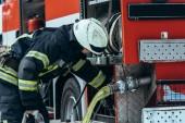 hasič v ochranné uniformě kontrola vodní hadice v autě na ulici