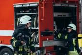 mužské hasič v uniformě držení hadice vody, zatímco kolega kontroly zařízení v autě na ulici