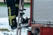 oříznuté záběr hasič v ochranné jednotné postavení na truck žebříku na ulici