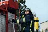 Feuerwehrfrau mit Feuerlöscher auf dem Rücken steht auf Feuerwehrauto auf Straße