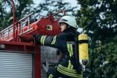 Fotografie ženské hasič s hasicí přístroj na zpět stojící na hasičské auto na ulici