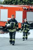 Hasiči v ohnivzdorné uniformě s přilby chůzi na ulici se hasičský vůz za