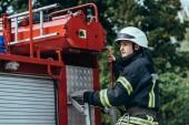 mužské hasič v ochranné přilbě stojící auta na ulici