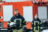 Selektivní fokus hasičů v ohnivzdorné uniformě na ulici s hasičský vůz za