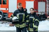 portrét hasičů v ohnivzdorné jednotné stojící na ulici s hasičský vůz za