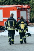Fotografie back view of firefighters in fireproof uniform walking on street with fire truck behind