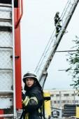 Fotografie ženské hasič v uniformě a helmu uhýbaje zatímco kolega, stojící na žebříku na ulici