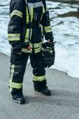 Fotografie částečný pohled ženské hasič v ohnivzdorné uniformě s rukavice v ruce stojí na steet s pěnou