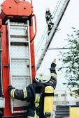 zadní pohled na ženské hasič s hasicí přístroj na záda ukázal svému kolegovi na žebříku na ulici