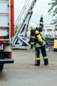 Fotografie rear view of firefighter in uniform and helmet with fire extinguisher on back gesturing on street