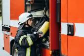ženské hasič v ochranné uniformě uvedením hasicí přístroj do kamionu na ulici