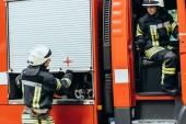 Hasiči v ochranných uniformu a přileb na hasičské auto na ulici