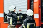 částečný pohled hasičů v přilbách v hasičské auto na ulici