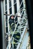 ženské hasič v ochranné uniformě a helmu stojící na žebříku na ulici
