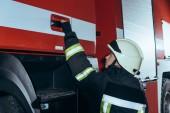 boční pohled na ženské hasič držící kliku truck hasiči