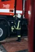 ženské hasič v ochranné jednotné dostává do kamionu na hasičské stanici