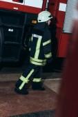 Fotografie ženské hasič v uniformě a přilbu na požární stanici
