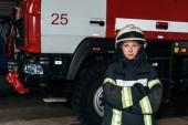 portrét ženské hasič v přilbě s rukama přes stojící na požární stanici s autem za