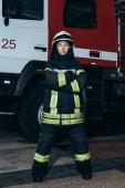 Fotografie ženské hasič v přilbě s rukama přes stojící na požární stanici s vozem za