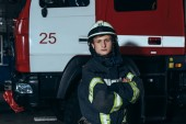 portrait of fireman in protective uniform and helmet with arms crossed at fire department