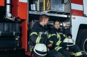 Hasiči v ochranné uniformě mají rozhovor v blízkosti kamionu na hasičské stanici