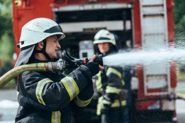 sokakta yangın söndürme su hortumu ile itfaiye eri ve seçici odak
