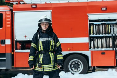 female firefighter in protective uniform standing on street with red fire truck behind