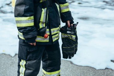 partial view of female firefighter in fireproof uniform with gloves in hand standing on steet with foam