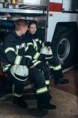Hasiči v ochranných uniformě bavit u kamionu na hasičské stanici