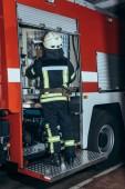 zadní pohled na hasiče v ohnivzdorné uniformu a helmu stojící poblíž truck na hasičské stanici