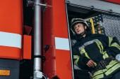nízký úhel pohledu hasič v helma koukal na hasiče