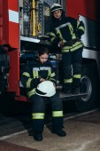 Hasiči v ochranném jednotné poblíž kamionu u hasiče