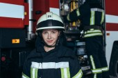 smiling female firefighter in helmet looking at camera with colleague checking equipment behind at fire station