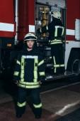 usmívající se žena hasič při pohledu na kameru, zatímco kolega kontroly zařízení v autě na hasiče