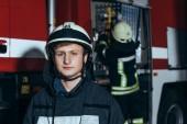 mužské hasič v přilbě s kolegou kontrola zařízení za na požární stanici při pohledu na fotoaparát
