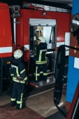 Fotografie částečný pohled hasičů v ohnivzdorné uniformě a přileb na hasičské stanici